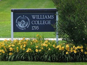 Williams College placard among a plot of daisies in bloom.